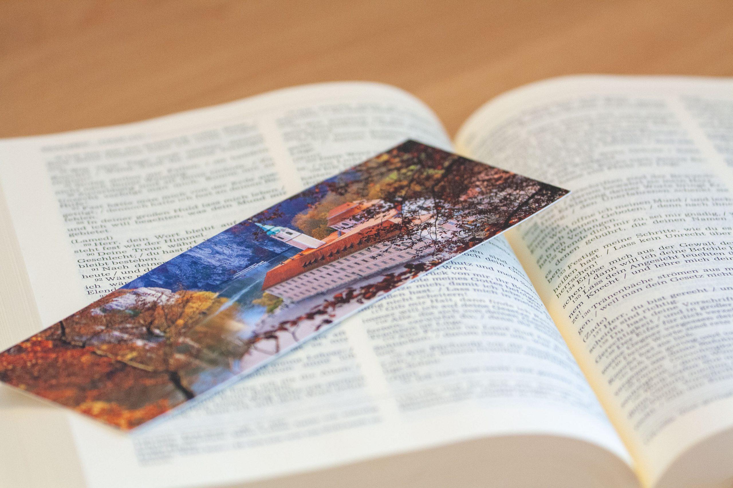Aufgeschlagene Bibel mit Lesezeichen auf dem das Klsoter Weltenburg im Herbst zu sehen ist