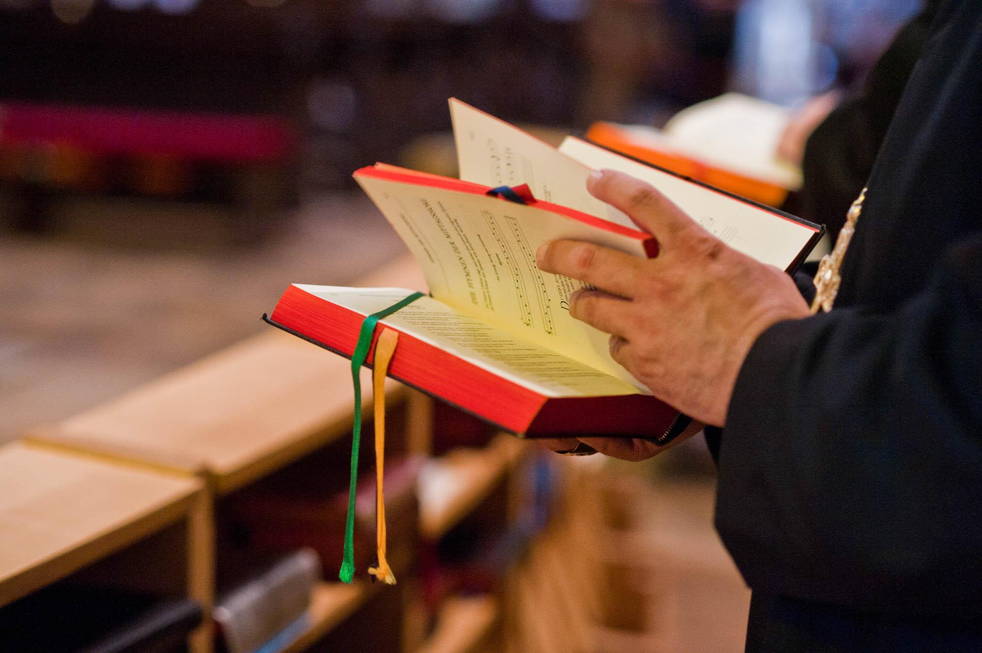 Ein Mönch blättert in einem Choralbuch